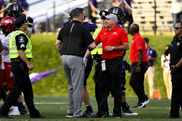 Northwestern head coach Pat Fitzgerald, center left, and UNLV head coach Troy Sanchez shake hands after an NCAA college football game, Saturday, Sept. 14, 2019, in Evanston, Ill. Northwestern won 30-14. (AP Photo/Matt Marton)
