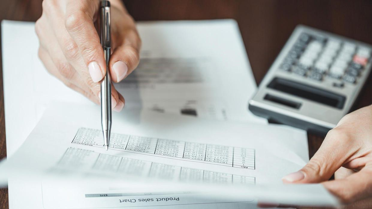 Close up of businesswomans hand with pen doing some financial calculations.