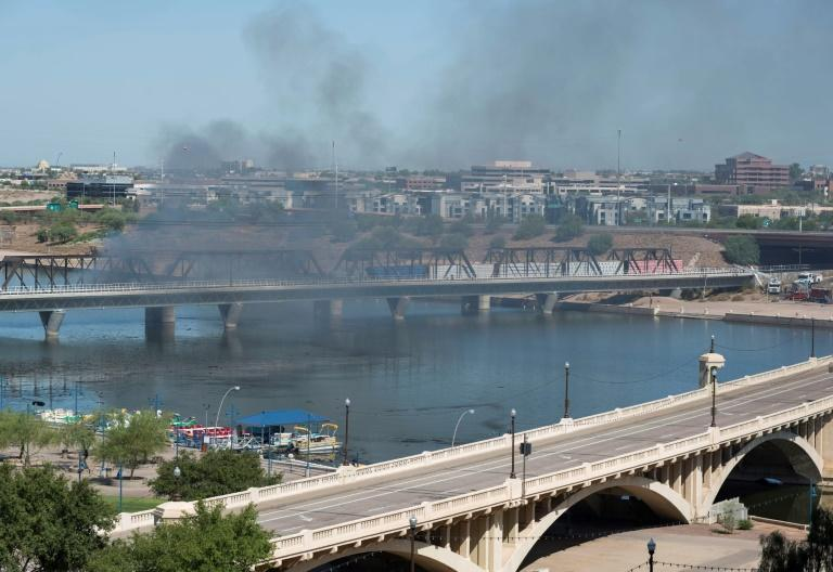 Smoke can be seen from a train derailment and fire along a bridge over Tempe Town Lake in Tempe, Arizona July 29, 2020. (AFP Photo/Laura Segall)