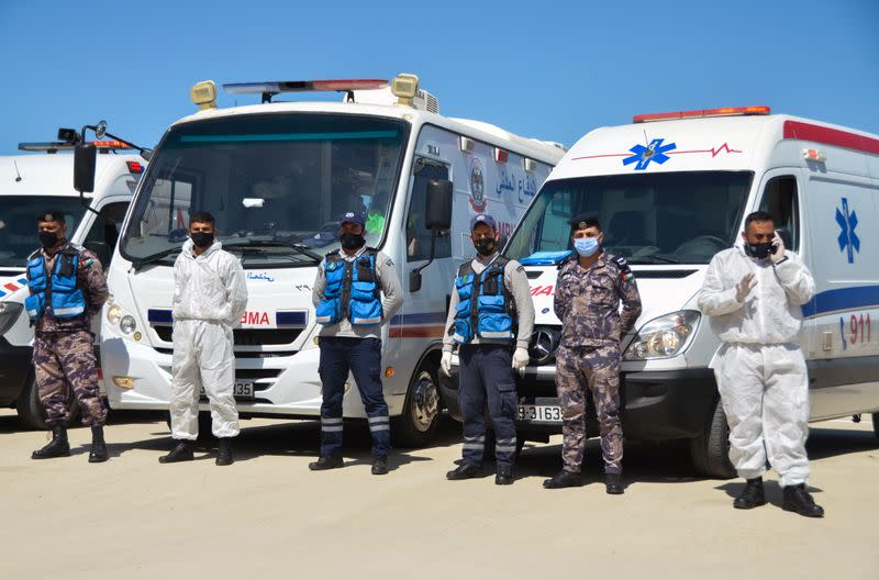 Civil defense members stand outside the new Salt government hospital in the city of Salt