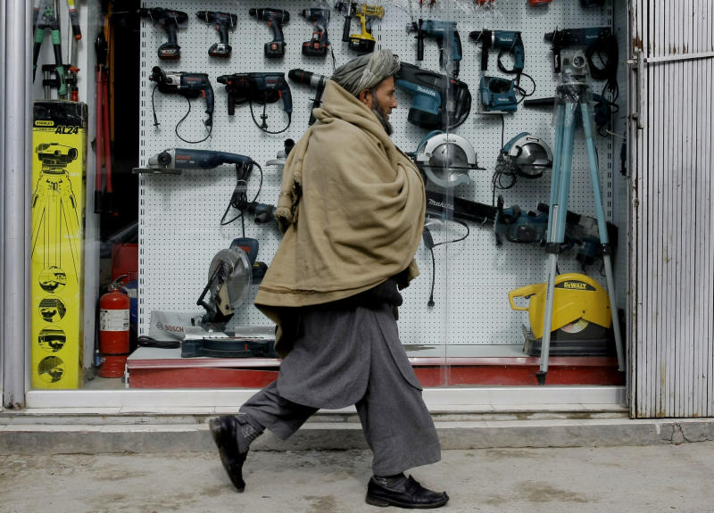 ADVANCE FOR SUNDAY JAN. 27 - In this Tuesday, Jan. 22, 2013 photo, An Afghan man walks past a shop selling tools made in China in Kabul, Afghanistan. China, long a bystander to the bloody conflict in neighboring Afghanistan, is accelerating its involvement as U.S.-led forces prepare to withdraw, attracted by its vast, untapped mineral resources and concerned that post-2014 chaos could fuel its own Islamist insurgents. (AP Photo/Musadeq Sadeq)