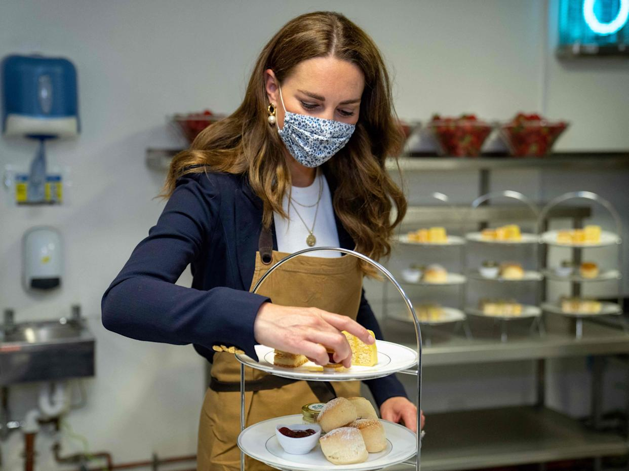 Britain's Catherine, Duchess of Cambridge, Patron of the All England Lawn Tennis Club, helps prepare cakes for a cream tea in the Wingfield kitchen during her visit on the fifth day of the 2021 Wimbledon Championships at The All England Tennis Club in Wimbledon, southwest London, on July 2, 2021. - RESTRICTED TO EDITORIAL USE (Photo by AELTC/Thomas Lovelock / POOL / AFP) / RESTRICTED TO EDITORIAL USE (Photo by AELTC/THOMAS LOVELOCK/POOL/AFP via Getty Images)