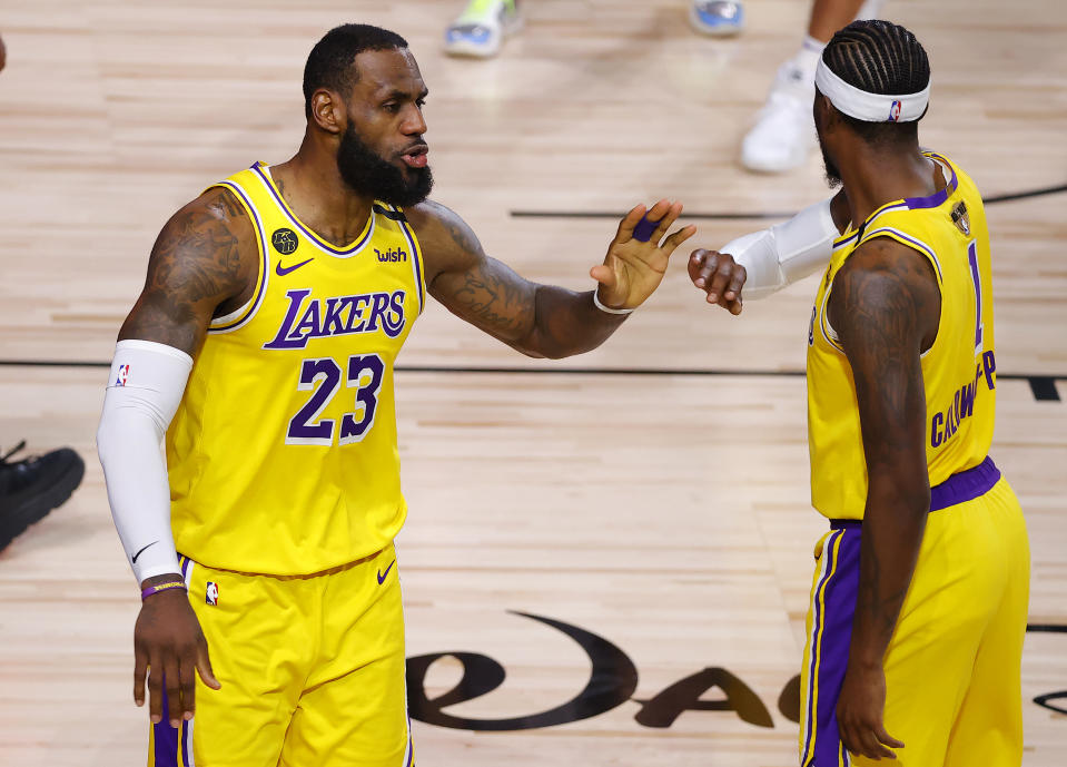 LeBron James #23 of the Los Angeles Lakers reacts with Kentavious Caldwell-Pope #1 of the Los Angeles Lakers after drawing a foul during the fourth quarter against the Miami Heat in Game Four of the 2020 NBA Finals