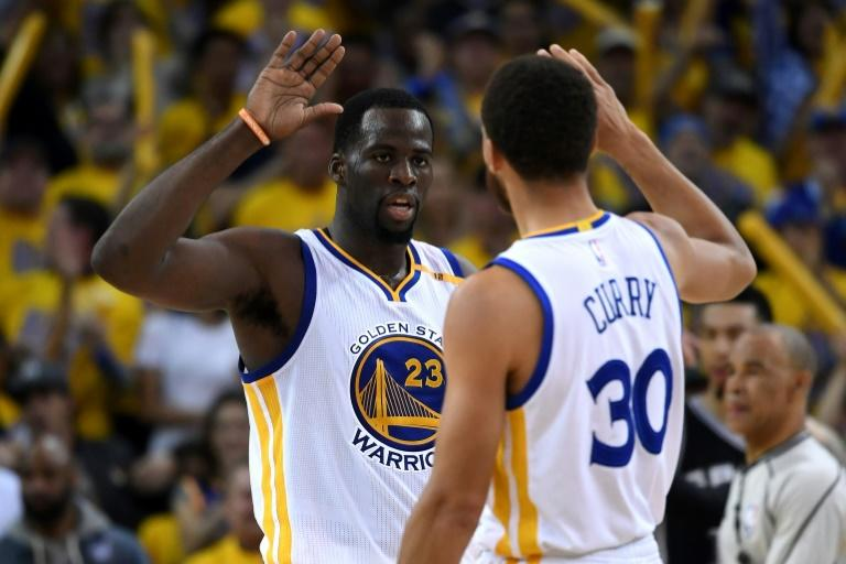 Draymond Green (L) and Stephen Curry of the Golden State Warriors celebrate after a basket against the San Antonio Spurs in Game One of the NBA Western Conference Finals, at ORACLE Arena in Oakland, California, on May 14, 2017