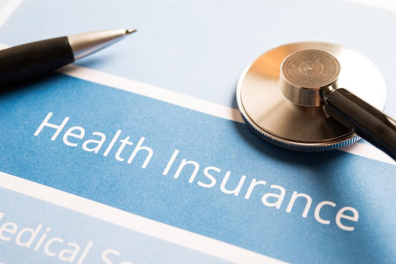 """Document with """"health insurance"""" as heading and a pen and stethoscope on top."""