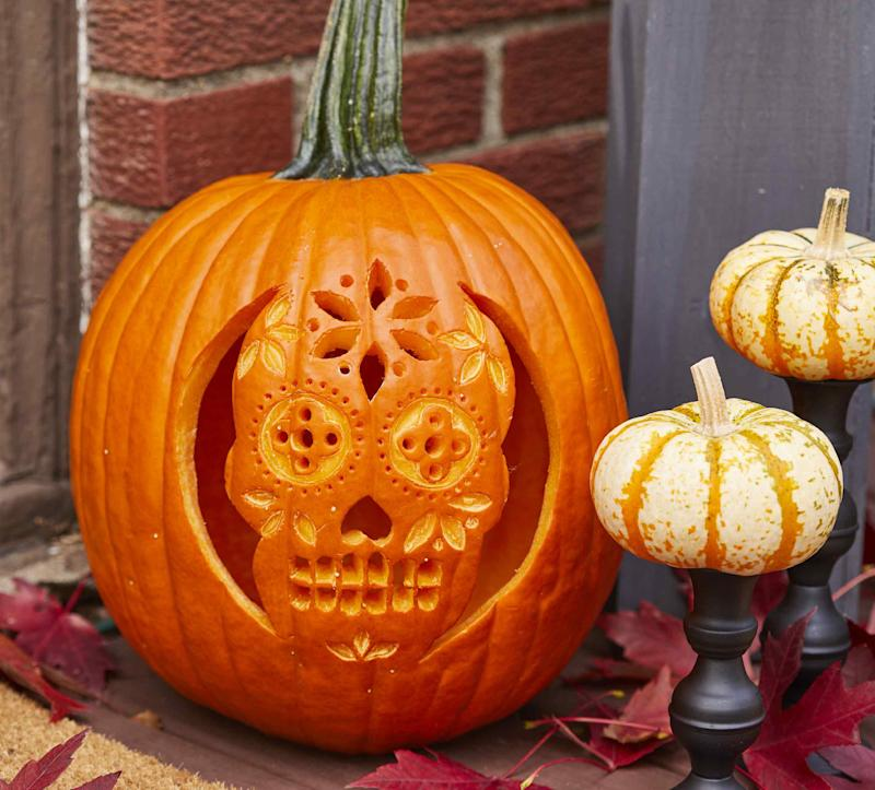 orange pumpkin with a sugar skull carved in the front of it, sitting on a halloween front porch with other small pumpkins