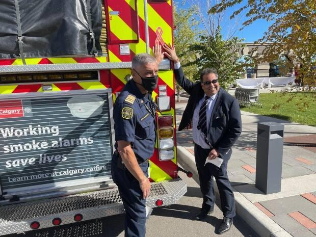 Calgary Mayor Naheed Nenshi and Calgary Fire Department Chief Steve Dongworth pose to show the new orange ribbon decals that will be placed on all city vehicles to show the city's commitment to remembrance, truth and reconciliation with Indigenous people. (Scott Dippel/CBC - image credit)