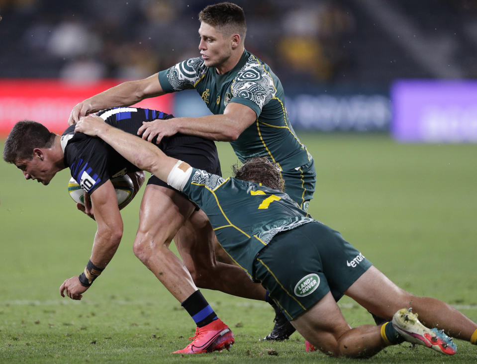 Argentina's Bautista Delguy, left, is tackled by Australia's Michael Hooper, right, and James O'Connor during their Tri-Nations rugby union match in Sydney, Australia, Saturday, Dec. 5, 2020. (AP Photo/Rick Rycroft)