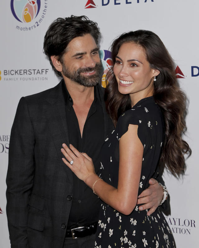 """<p>The look of love! The <em>Fuller House</em> star gazed at his <a href=""""https://www.yahoo.com/celebrity/john-stamos-engaged-model-caitlin-mchugh-said-yes-114841103.html"""" data-ylk=""""slk:new fiancée;outcm:mb_qualified_link;_E:mb_qualified_link"""" class=""""link rapid-noclick-resp newsroom-embed-article"""">new fiancée</a>, Caitlin McHugh, as the <a href=""""https://www.yahoo.com/lifestyle/john-stamos-cloud-nine-now-063404400.html"""" data-ylk=""""slk:loved-up duo;outcm:mb_qualified_link;_E:mb_qualified_link"""" class=""""link rapid-noclick-resp newsroom-embed-article"""">loved-up duo</a> attended the Mothers2Mothers and the Elizabeth Taylor AIDS Foundation benefit dinner in Beverly Hills on Tuesday. McHugh looked absolutely lit up with happiness, and her glow could only be rivaled by the beauty of the diamond on her finger. (Photo: Tibrina Hobson/Getty Images) </p>"""