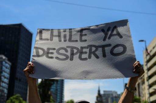 "A demonstrator in Santiago holds a sign reading ""Chile has awakened"""