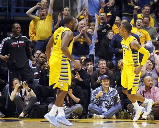 Marquette's Vander Blue (2) celebrates a play with Junior Cadougan (5) against Seton Hall during the second half of an NCAA college basketball game, Tuesday, Jan. 31, 2012, in Milwaukee. At left is Miami Heat's Dwyane Wade, who attended college at Marquette. (AP Photo/Jeffrey Phelps)
