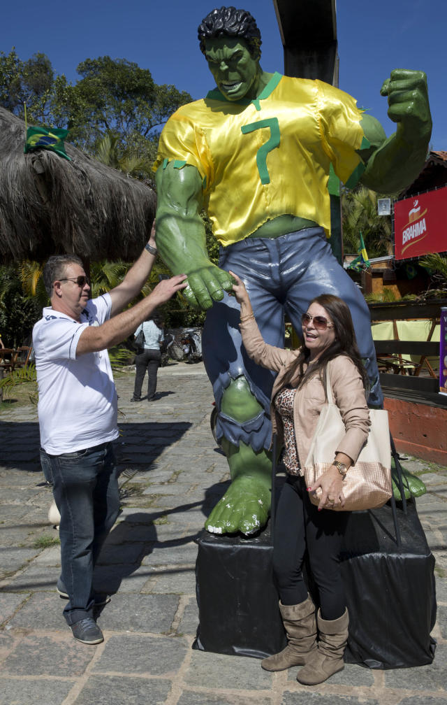 Soccer fans pose for pictures with a statue of super hero Hulk near the Granja Comary training center, where Brazil is training during the World Cup, in Teresopolis, Brazil, Wednesday, June 25, 2014. The statue is in tribute to Brazil's soccer player named Hulk. (AP Photo/Andre Penner)