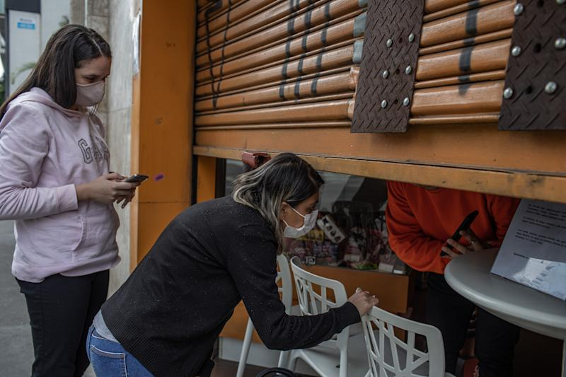 SAO PAULO, BRAZIL - MAY 07: A customer wearing a face mask buys at a store with a half closed curtain on May 7, 2020 in Sao Paulo, Brazil. The Government of the State of São Paulo has decreed the mandatory use of face masks in the streets. (Photo by Victor Moriyama/Getty Images)