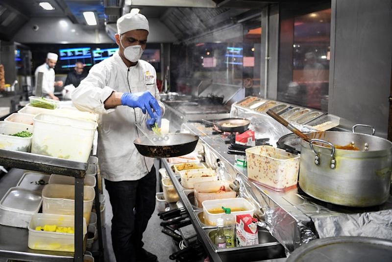 Kitchen staff at the Kebabish Grill restaurant in Glasgow wear masks as they prepare foo