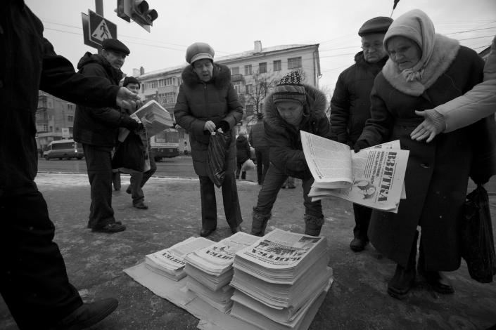 In this Nov. 14, 2012, photo, residents of Cheboksary swarm around free copies of the news paper The Bribe in Cheboksary, the capital city of Chuvashia, Russia. Eduard Mochalov has found a new lease on life as a crusading journalist investigating corruption in his native region, fueled by tips from disgruntled businessmen and government workers. Undeterred by a system where the law is selectively used to protect the powerful and crack down on critics, Mochalov has quickly earned cult status _ not to mention the ire of countless local officials _ throughout the small province of Chuvashia. (AP Photo/Alexander Zemlianichenko)
