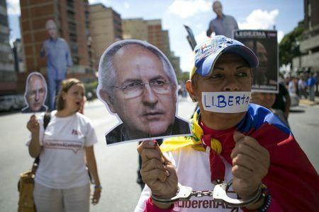 FILE PHOTO: Supporters of arrested Caracas metropolitan mayor Antonio Ledezma hold up a cutout of his face during a gathering in his support in Caracas, Venezuela, August 19, 2015. REUTERS/Marco Bello/File Photo
