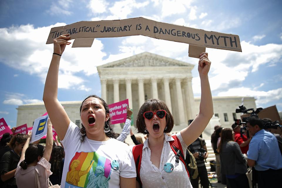 <p>Protesters Celina Scott-Buechler (R) and Lisset Pino (L) demonstrate against U.S. President Trump's travel ban as protesters gather outside the U.S. Supreme Court following a court issued immigration ruling June 26, 2018 in Washington, D.C. (Photo: Win McNamee/Getty Images) </p>