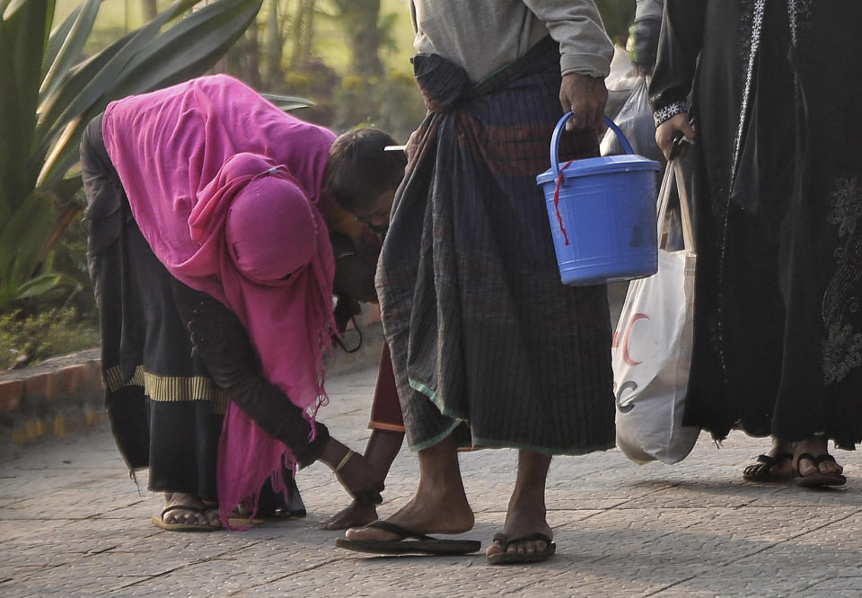 A Rohingya woman looks at a child's leg as they walk to board a naval vessel to be relocated to to the island of Bhasan Char, in Chattogram, Bangladesh, Saturday, Jan. 30, 2021. Authorities in Bangladesh sent a group of Rohingya refugees to a newly developed island in the Bay of Bengal on Saturday despite calls by human rights groups for a halt to the process. The government insists the relocation plan is meant to offer better living conditions while attempts to repatriate more than 1 million refugees to Myanmar would continue. (AP Photo/Azim Aunon)