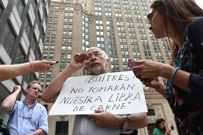 "A protestor holds a sign that translates as ""Vultures! Don't take our pound of meat"" outside the office building of mediator Daniel Pollack July 30, 2014 in New York (AFP Photo/Stan Honda)"