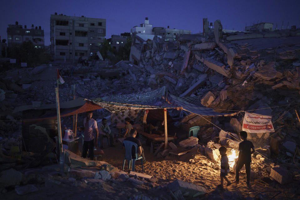 Palestinians sit inside a makeshift tent built amid the rubble of their home, destroyed by an airstrike in Beit Lahia, northern Gaza Strip, Friday, June 4, 2021. A truce that ended an 11-day war between Gaza's Hamas rulers and Israel has so far held but it did not address any of the deeper issues plaguing the Israeli-Palestinian conflict. (AP Photo/Felipe Dana)