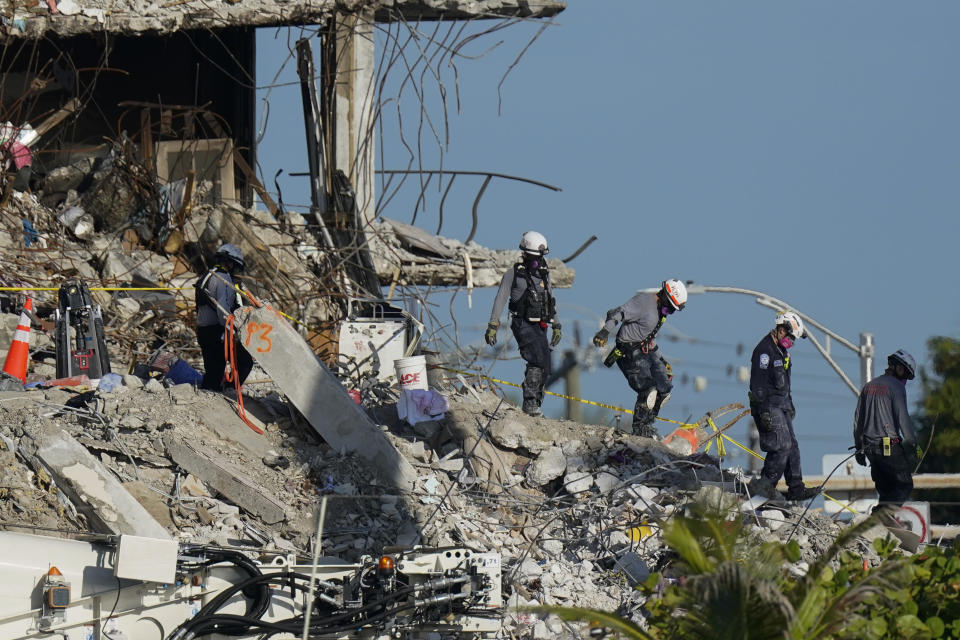Search and rescue workers descend from the rubble pile at the Champlain Towers South condo building, where scores of people remain missing one week after it partially collapsed, Friday, July 2, 2021, in Surfside, Fla. (AP Photo/Mark Humphrey)