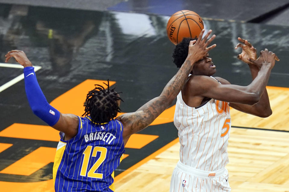 Indiana Pacers forward Oshae Brissett (12) and Orlando Magic center Mo Bamba (5) battle for a rebound during the first half of an NBA basketball game, Sunday, April 25, 2021, in Orlando, Fla. (AP Photo/John Raoux)