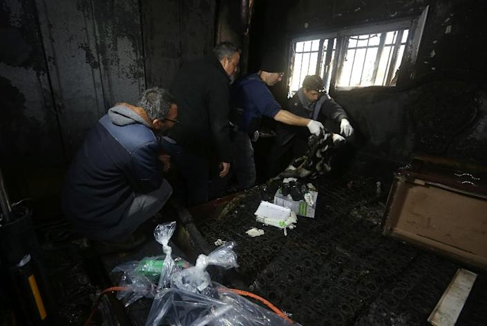 Israeli police members inspect the damage inside a Palestinian burnt-out house belonging to a key witness to an arson attack which took place last year by Jewish extremists that killed a Palestinian family, in the village of Duma, on March 20, 2016. (AFP Photo/Jaafar Ashtiyeh)