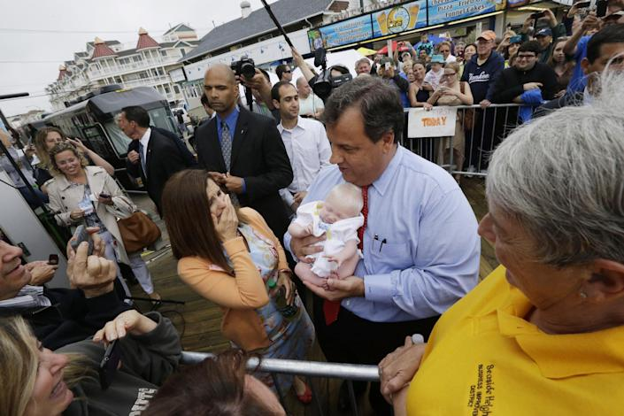 New Jersey Gov. Chris Christie, right, holds 6-week-old Willow DeParre, as first lady Mary Pat Christie looks on as they greet people during the opening of the New Jersey shore, Friday, May 24, 2013, in Seaside Heights, N.J. Christie cut a ribbon to symbolically reopen the state's shore for the summer season, seven months after being devastated by Superstorm Sandy. Several beach communities have annual beach ribbon cuttings, announcing they are back in business. But this year's ceremonies are more poignant seven months after a storm that did an estimated $37 billion of damage in the state. (AP Photo/Julio Cortez)