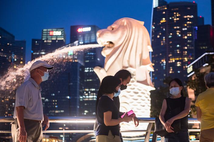 Vistors walk past the Merlion at the Marina Bay on 18 July, 2021. (PHOTO: Getty Images)