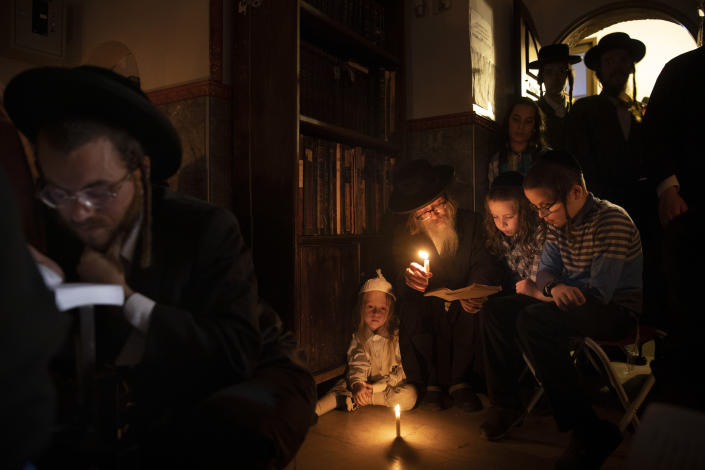 Ultra-Orthodox Jewish men and children read by candle light from the book of Eicha (Book of Lamentations) during the annual Tisha B'Av (Ninth of Av) fasting and a memorial day, commemorating the destruction of ancient Jerusalem temples, in the Ultra-Orthodox neighborhood of Mea Shearim in Jerusalem, Saturday, July 17, 2021. (AP Photo/Oded Balilty)