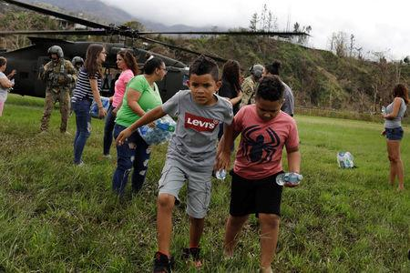 """Boys carry water away from an HH-60 Blackhawk helicopter after soldiers working with the U.S. Army's 101st Airborne Division's """"Dustoff"""" unit dropped off relief supplies during recovery efforts following Hurricane Maria, in Jayuya, Puerto Rico, October 5, 2017. REUTERS/Lucas Jackson"""