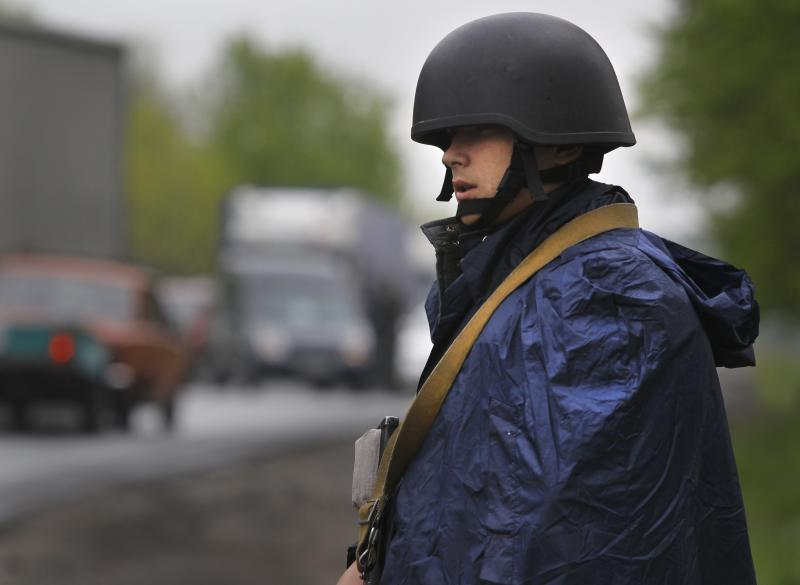 Ukrainian government soldier guards a checkpoint near the village of Dolina, 30 kilometers (18 miles) from Slovyansk, eastern Ukraine, Tuesday, April 29, 2014. The European Union on Tuesday released the names of 15 new targets of sanctions because of their roles in the Ukraine crisis. The list includes Gen. Valery Gerasimov, chief of the Russian General Staff and first deputy defense minister, and Lt. Gen. Igor Sergun, identified as head of GRU, the Russian military intelligence agency. (AP Photo/Sergei Grits)