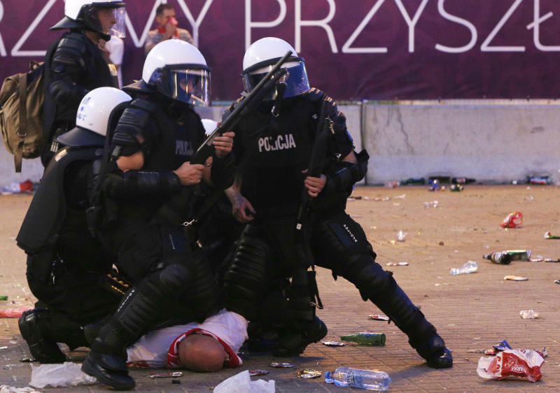 Police arrest a Polish fan during clashes between young Poles and the police during the Euro 2012 soccer championship group a match between Poland and Russia in downtown Warsaw, Poland , Tuesday, June 12, 2012. (AP Photo/Czarek Sokolowski)