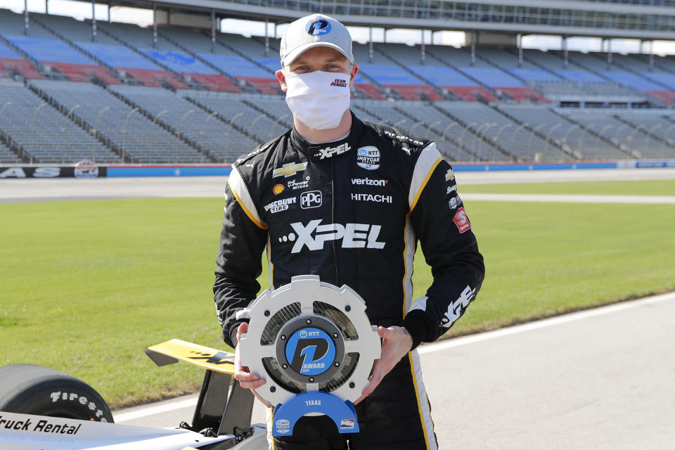 Josef Newgarden poses for photos on pit road after earning the pole award for an IndyCar auto race at Texas Motor Speedway in Fort Worth, Texas, Saturday, June 6, 2020. (AP Photo/Tony Gutierrez)