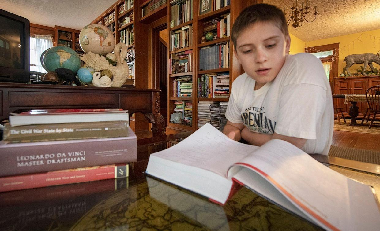 Tyler Spangler, age 12, looks at the course book his mother bought for a Penn State York calculus with analytic geometry class he starts in a few weeks. Behind him are just a few of the globes he has collected because he loves traveling and geography.