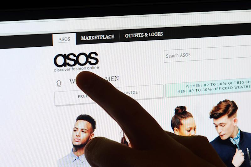 A finger points to the logo on the Asos website