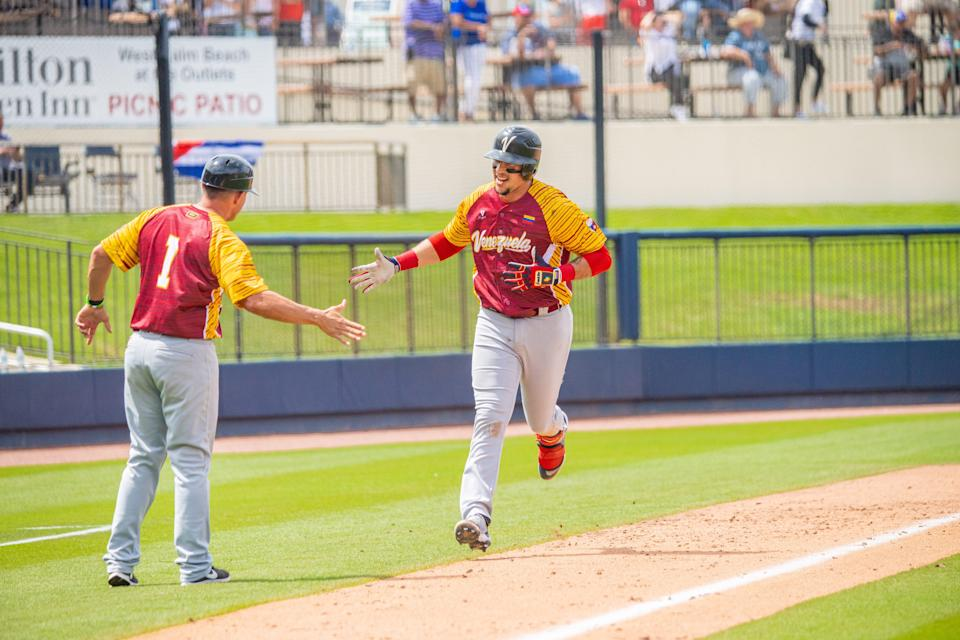 Hernan Perez is congratulated by the third-base coach after hitting a solo home run to help Venezuela hold off Cuba during Monday's game at the Ballpark of the Palm Beaches