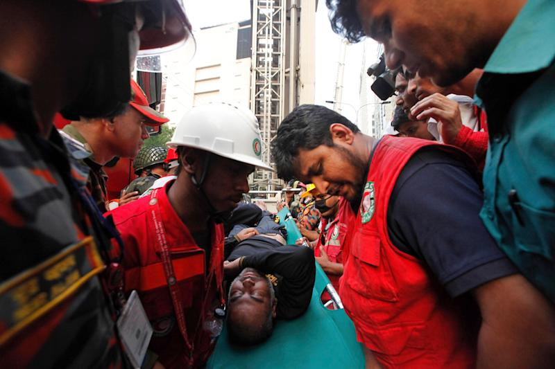 Firefighters evacuate an injured after a multi-storied office building caught fire in Dhaka, Bangladesh, March 28, 2019. (AP Photo/Mahmud Hossain Opu )