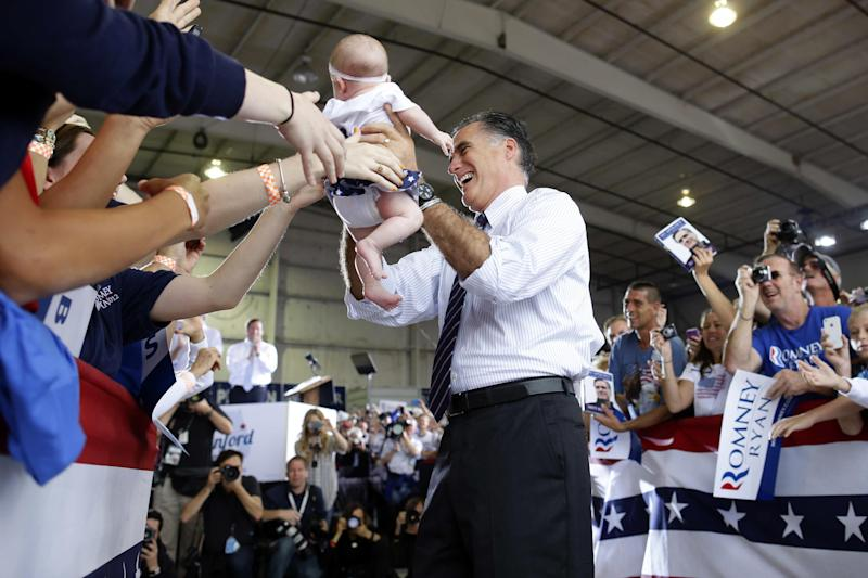 Republican presidential candidate, former Massachusetts Gov. Mitt Romney picks up a baby as he arrives at a Florida campaign rally at Orlando Sanford International Airport, in Sanford, Fla., Monday, Nov. 5, 2012. (AP Photo/Charles Dharapak)