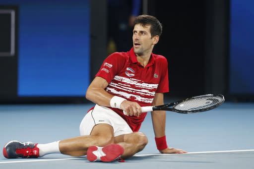 Novak Djovovic of Serbia falls on court after missing a shot against Rafael Nadal of Spain during their ATP Cup tennis match in Sydney, Sunday, Jan. 12, 2020. Djovovic went on to win the match. (AP Photo/Steve Christo)