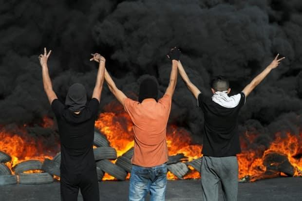 Palestinian demonstrators in occupied West Bank raise their arms during a protest Sunday over tensions in East Jerusalem and the escalation of fighting between Israel and Hamas. Protests, riots and confrontations have broken out in the occupied territories and mixed Jewish-Arab cities in Israel since the fighting escalated last week. (Ammar Awad/Reuters - image credit)