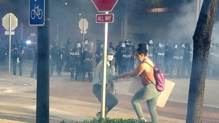 LaToya Ratlieff flees tear gas moments before she is hit in the face with a rubber bullet.