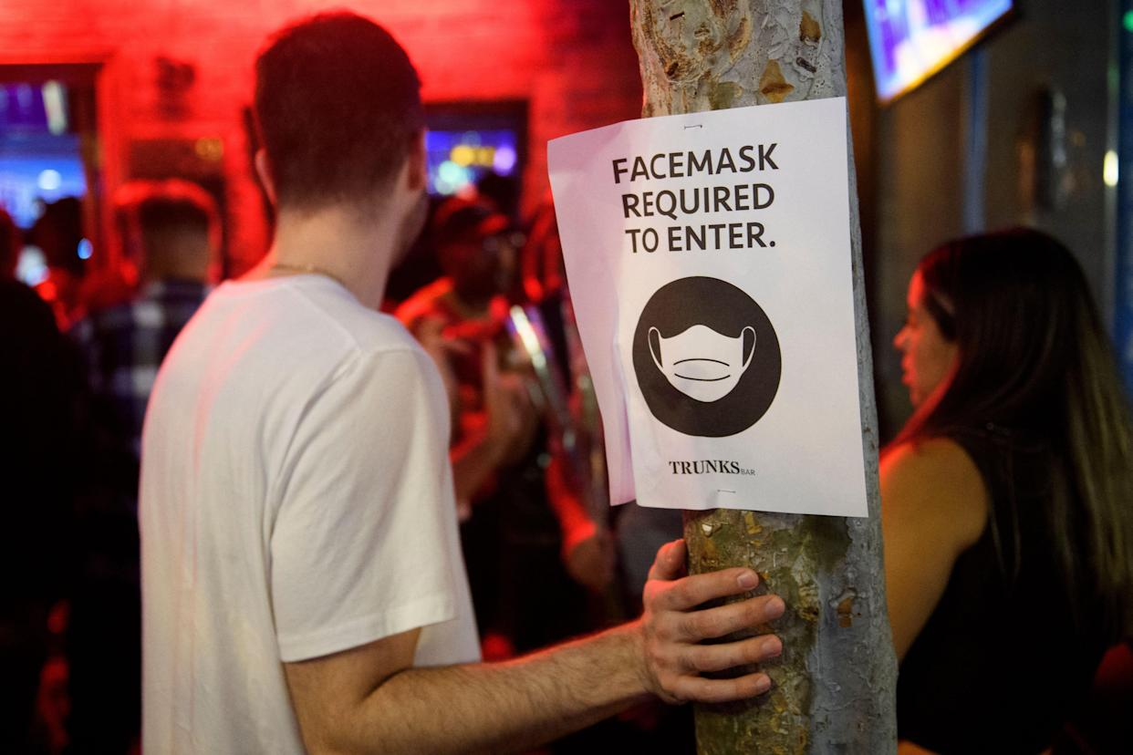 Face mask signage is displayed outside the Trunks bar after midnight early Sunday morning on July 18, 2021 in West Hollywood, California. - Wearing a face mask at indoor public establishments will once again be mandatory in Los Angeles County starting at 11:59 pm July 17, 2021 for both vaccinated and unvaccinated people due to a steady increase in Covid-19 infections and hospitalizations, health authorities said. (Photo by Patrick T. FALLON / AFP) (Photo by PATRICK T. FALLON/AFP via Getty Images)