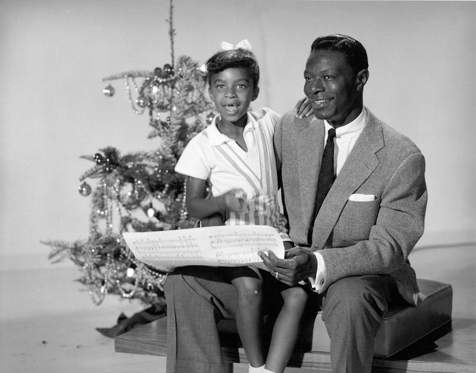 <p>Natalie Cole gets into the holiday spirit by singing carols with her famous father, musician Nat King Cole. The two posted up in front of the tree in 1970.</p>