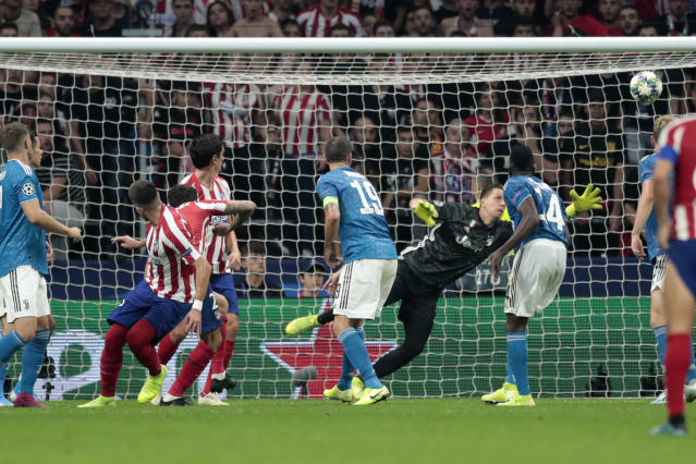 Atletico Madrid's Hector Herrera, second left, watches as his header goes into the net passing Juventus' goalkeeper Wojciech Szczesny to score his side's second goal during the Champions League Group D soccer match between Atletico Madrid and Juventus at the Wanda Metropolitano stadium in Madrid, Spain, Wednesday, Sept. 18, 2019. (AP Photo/Bernat Armangue)