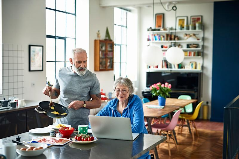 Retired couple in modern kitchen on the weekend, woman surfing the web, man holding frying pan and serving scrambled eggs