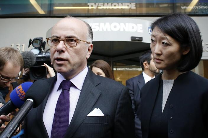 French Interior Minister Bernard Cazeneuve (L) and Culture minister Fleur Pellerin talk to the press after visiting the TV5Monde headquarters in Paris on April 9, 2015 (AFP Photo/Thomas Samson)