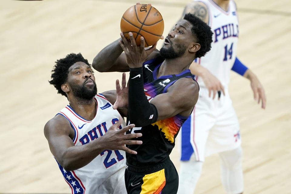 Phoenix Suns center Deandre Ayton shoots over Philadelphia 76ers center Joel Embiid (21) during the second half of an NBA basketball game, Saturday, Feb. 13, 2021, in Phoenix.(AP Photo/Matt York)