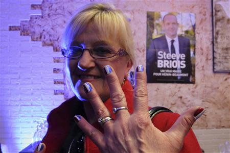 Martine, a 54-year-old France's far-right National Front political party political activist, shows her nails painted with the French national flag at the FN headquarters in Henin Beaumont, Northern France, March 23, 2014. REUTERS/Pascal Rossignol