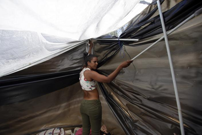 <p>A Venezuelan migrant woman makes a makeshift tent after walking from her homeland through Colombia to Quito, Ecuador, Thursday, Aug. 9, 2018. (Photo: Dolores Ochoa/AP) </p>